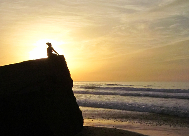 woman sitting on rock sunset shadow contemplation